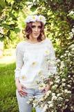 Mujer joven con una guirnalda de manzanillas en su cabeza por el árbol Fotografía de archivo