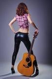 Mujer joven con una guitarra acústica en un fondo negro, posterior Fotografía de archivo libre de regalías