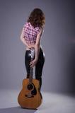 Mujer joven con una guitarra acústica en un fondo negro, posterior imagenes de archivo