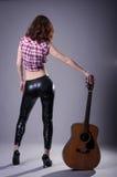 Mujer joven con una guitarra acústica en un fondo negro, posterior Fotos de archivo libres de regalías