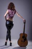 Mujer joven con una guitarra acústica en un fondo negro, posterior Fotografía de archivo