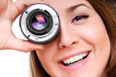 Mujer joven con una lente fotografía de archivo libre de regalías