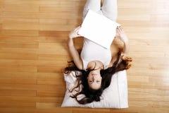 Mujer joven con una lona en blanco Fotos de archivo libres de regalías