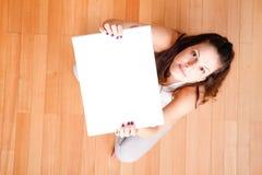 Mujer joven con una lona en blanco Imagen de archivo libre de regalías