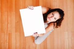 Mujer joven con una lona en blanco Foto de archivo libre de regalías