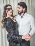 Mujer joven con una máscara del cordón y un baile tatuado del hombre en puertas Foto de archivo libre de regalías