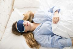 Mujer joven con una máscara del sueño fotos de archivo