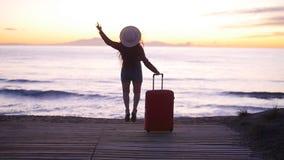 Mujer joven con una maleta en la playa soleada almacen de metraje de vídeo