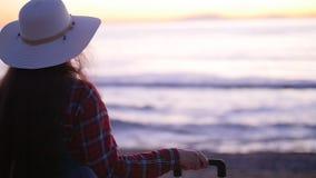 Mujer joven con una maleta en la playa soleada almacen de video