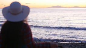 Mujer joven con una maleta en la playa soleada metrajes