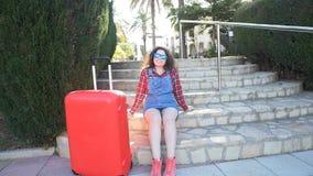 Mujer joven con una maleta en un centro turístico almacen de metraje de vídeo