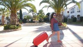 Mujer joven con una maleta en un centro turístico metrajes