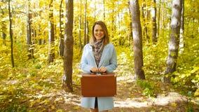 Mujer joven con una maleta en un parque del otoño almacen de video