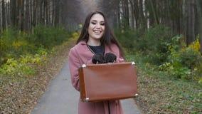 Mujer joven con una maleta en un parque del otoño metrajes