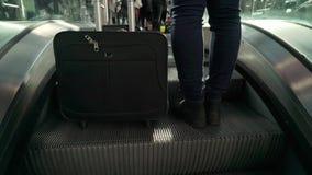 Mujer joven con una maleta que camina a la escalera móvil almacen de video