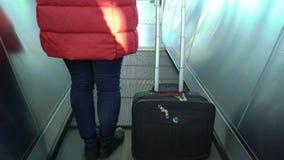 Mujer joven con una maleta que camina a la escalera móvil metrajes