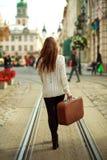 Mujer joven con una maleta que camina a través de la calle Imágenes de archivo libres de regalías
