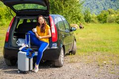 Mujer joven con una maleta que disfruta de la naturaleza mientras que se sienta en el tronco de coche en el top de la montaña imágenes de archivo libres de regalías