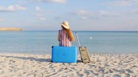 Mujer joven con una maleta que se sienta en la playa almacen de video