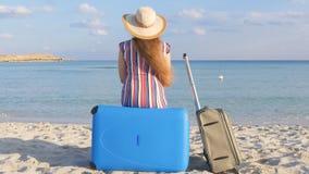 Mujer joven con una maleta que se sienta en la playa metrajes
