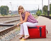 Mujer joven con una maleta roja Imágenes de archivo libres de regalías