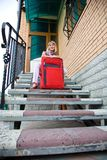 Mujer joven con una maleta roja Imagen de archivo
