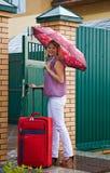 Mujer joven con una maleta roja Imagenes de archivo