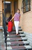 Mujer joven con una maleta roja Imagen de archivo libre de regalías