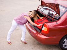 Mujer joven con una maleta roja en el coche Fotografía de archivo