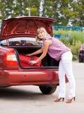 Mujer joven con una maleta roja en el coche Imagen de archivo