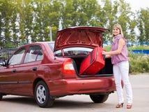 Mujer joven con una maleta roja en el coche Foto de archivo libre de regalías