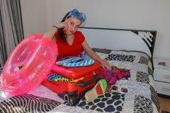 Mujer joven con una maleta roja, los viajes y la reconstrucción, turismo Muchacha y una maleta turista femenino hermoso con la ma Imágenes de archivo libres de regalías