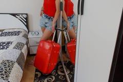 Mujer joven con una maleta roja, los viajes y la reconstrucción, turismo Muchacha y una maleta turista femenino hermoso con la ma Foto de archivo