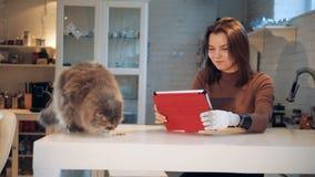 Mujer joven con una mano biónica y un gato cerca de ella