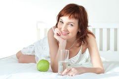 Mujer joven con una manzana verde y vidrio de agua imagen de archivo