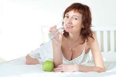 Mujer joven con una manzana verde y vidrio de agua foto de archivo libre de regalías