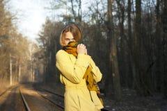 Mujer joven con una mitad de la cara ocultada por debajo una bufanda Foto de archivo