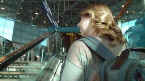 Mujer joven con una mochila que camina a la escalera móvil almacen de metraje de vídeo