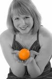 Mujer joven con una naranja Fotografía de archivo
