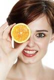 Mujer joven con una naranja Foto de archivo libre de regalías