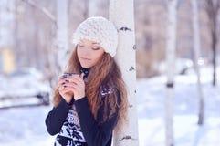 Mujer joven con una taza de bebida caliente en parque del invierno Foto de archivo libre de regalías