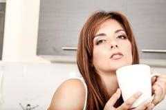Mujer joven con una taza de café Foto de archivo