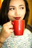 Mujer joven con una taza de café por la mañana Foto de archivo libre de regalías