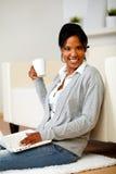 Mujer joven con una taza delante de su computadora portátil Foto de archivo libre de regalías