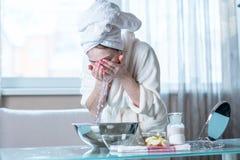 Mujer joven con una toalla en su cara que se lava principal con agua por la mañana Higiene y cuidado para la piel en casa fotos de archivo
