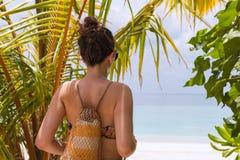 Mujer joven con una toalla que camina a la playa en un destino tropical fotografía de archivo libre de regalías