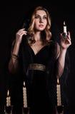 Mujer joven con una vela en oscuridad Fotos de archivo