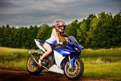 Mujer joven con una velocidad de la motocicleta Fotografía de archivo
