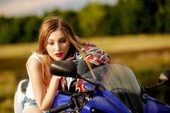 Mujer joven con una velocidad de la motocicleta Fotos de archivo libres de regalías