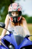 Mujer joven con una velocidad de la motocicleta Foto de archivo libre de regalías